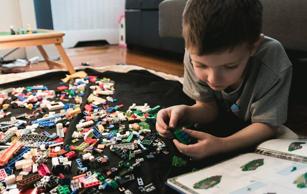 Kind kijkt in de beschrijving van de Lego set en bouwt een doos in elkaar van T-Bric abonnement van € 19,99